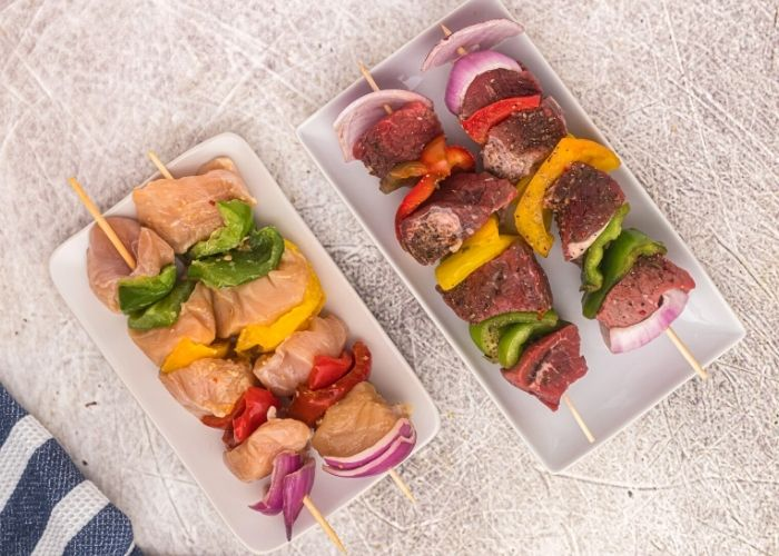 Side by side plates of uncooked chicken and steak cut into cubes, with bell peppers and onions on skewers.