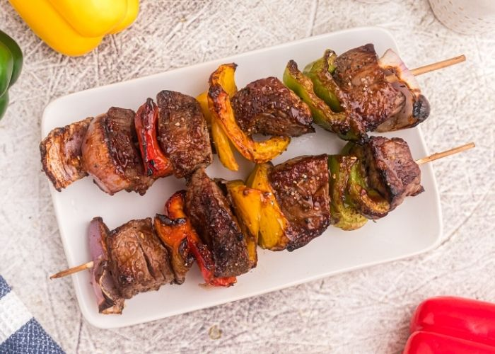 Beef kabobs with seasonings and bell peppers, onions, and BBQ sauce.