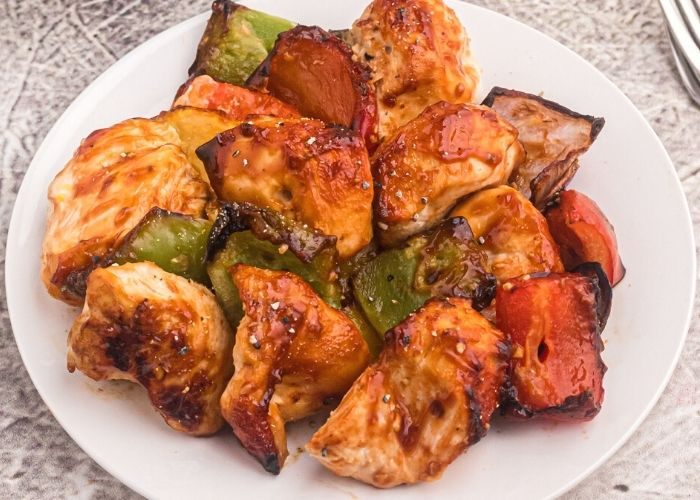 Juicy chicken and vegetables on a white plate, after being cooked on the skewer.