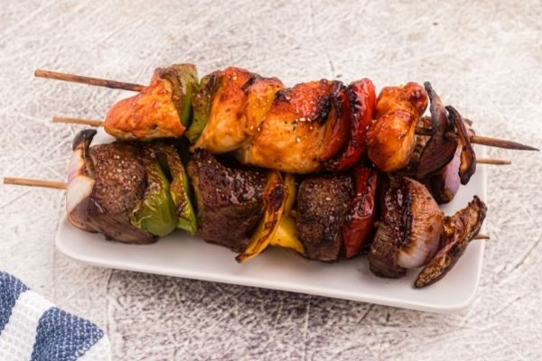 Chicken and steak, cooked on skewers with cut up bell peppers and onion.