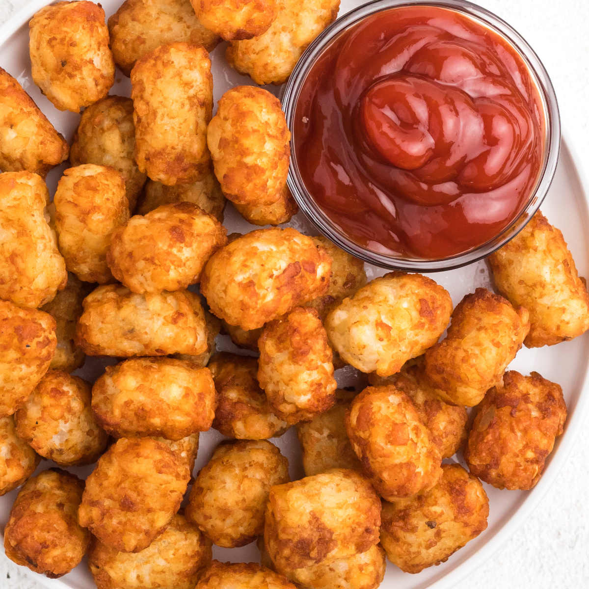 Tater Tots on a white plate that were made in the Air Fryer. A small bowl of ketchup on the side.