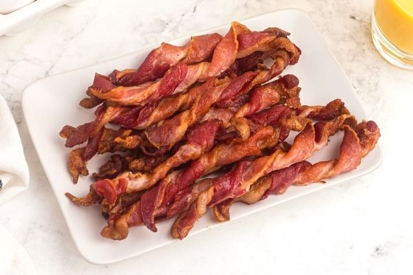 Crispy bacon twisted into curls and stacked on a white rectangle plate. Orange juice in a glass on the side.