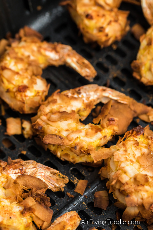 Cooked Coconut Shrimp in the basket of the air fryer.