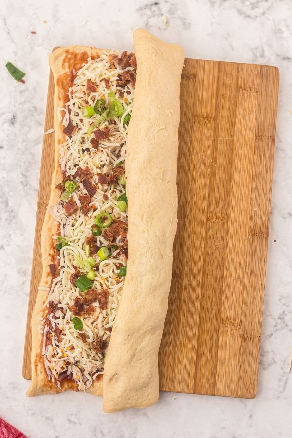 Rolled dough shaped into rectangle, then topped with sauce and cheese, shredded chicken, halfway rolled up.