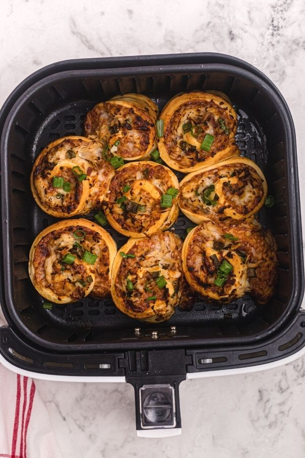 Cooked air fryer BBQ chicken pizza roles in the air fryer basket, sprinkled with chopped green onions.