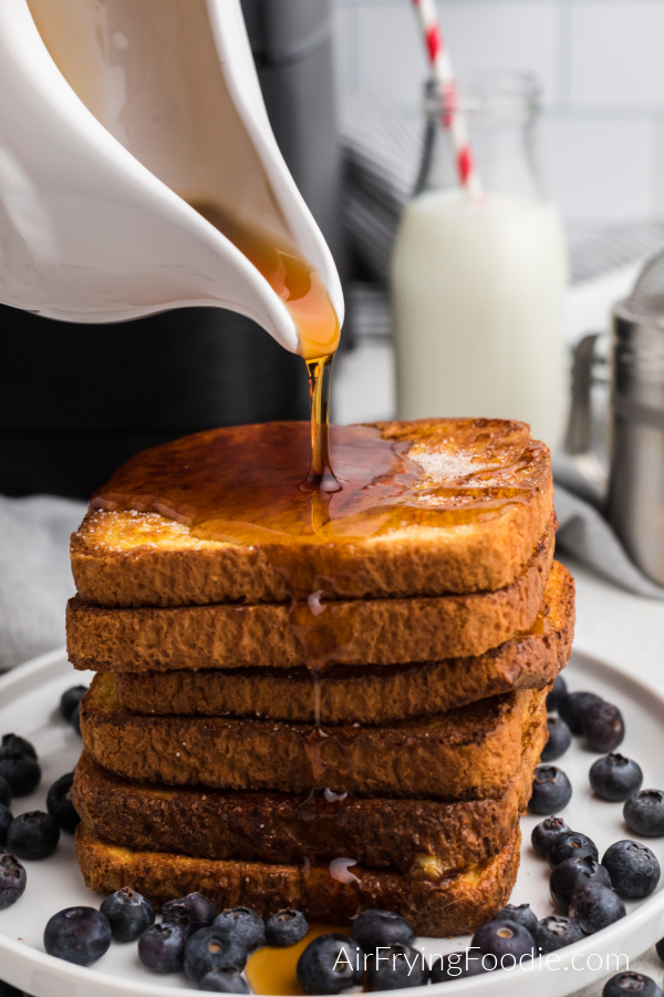 Stack of french toast with syrup being poured on top.