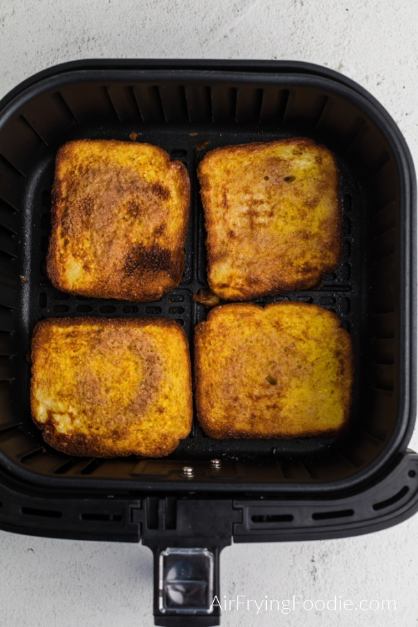 Cooked french toast in the basket of the air fryer.