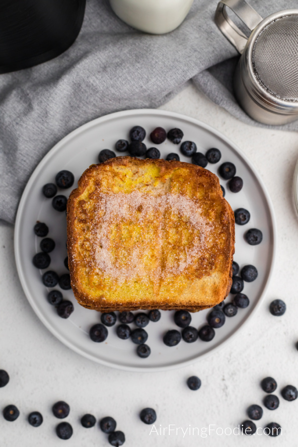 Stack of air fried french toast surrounded by blueberries on a white plate.