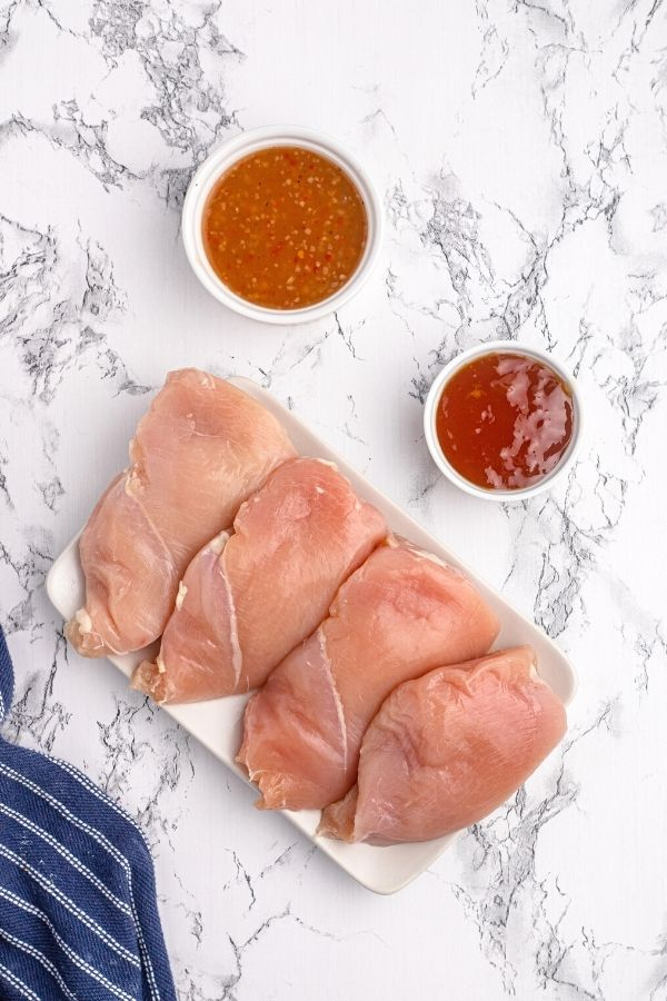 Ingredients to make glazed chicken on a white plate. Raw chicken, Italian dressing, and peach preserves.