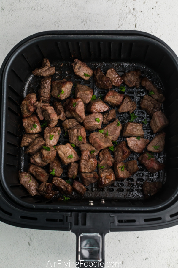Fully cooked steak bites in the basket of the air fryer.