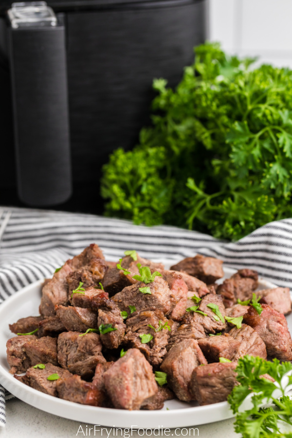 steak bites made in the air fryer on a white plate with fresh parsley sprinkled over the top.