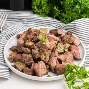 steak bites made in the air fryer and served on a white plate and topped with fresh parsley.