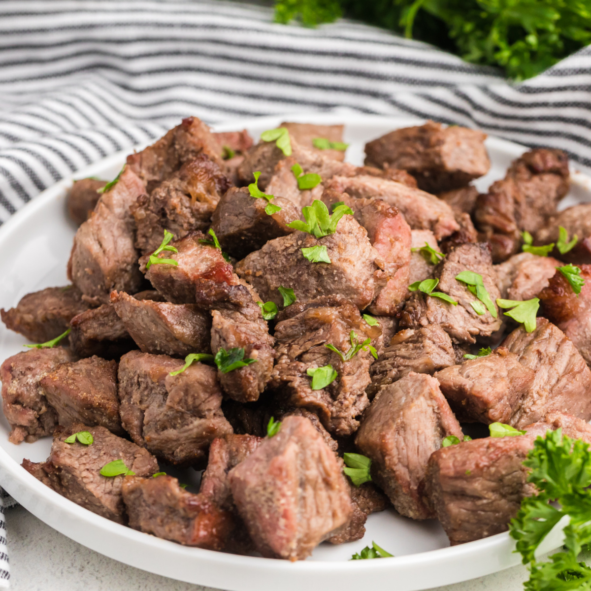 steak bites on a white plate and garnished with fresh parsley.