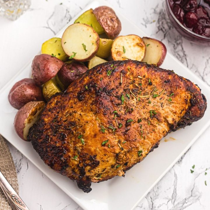 Close up photo of golden crispy turkey breast on a white plate and served with baby potatoes.