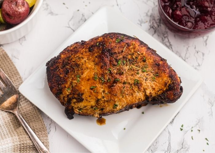 Golden crispy, and seasoned turkey breast, on a white plate with juices dripping.