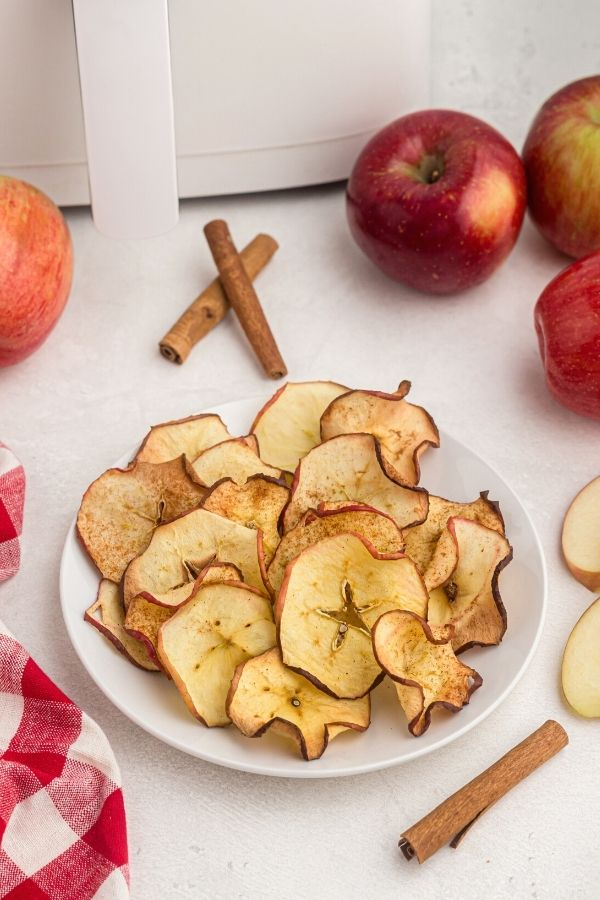 Crispy apple chips served on a white plate with cinnamon stick on the table near a red checkered napkin.