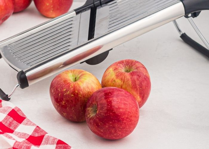 Red apples in front of a mandolin slicer with a red checked cloth on the table.