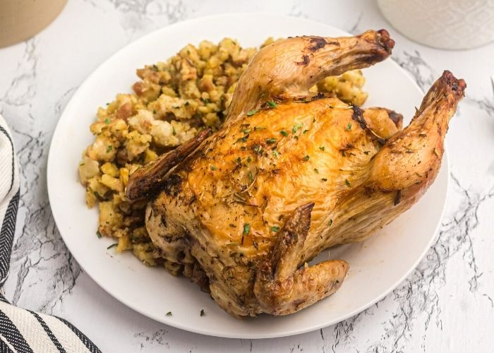 Crispy golden Cornish game hen served on a white plate with stuffing on the plate.
