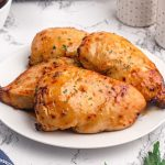 Golden chicken breasts cooked with a shiny glaze of peach preserves and seasonings.
