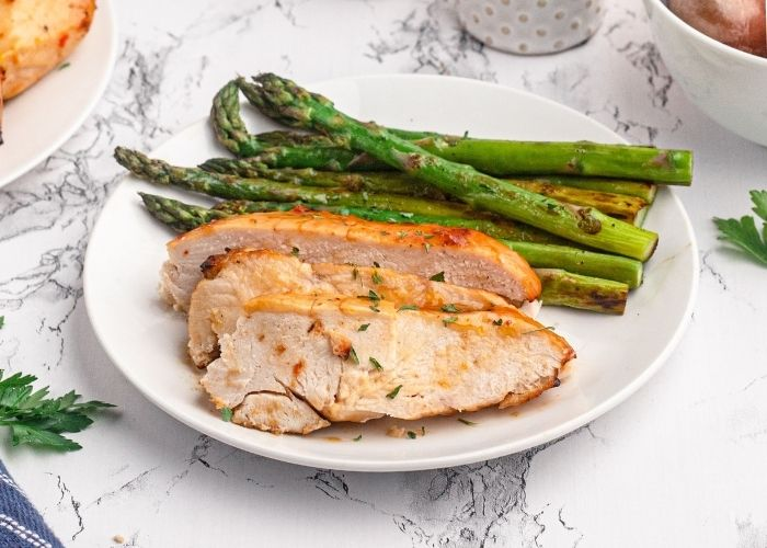 Sliced chicken breast served on a white plate with green asparagus.
