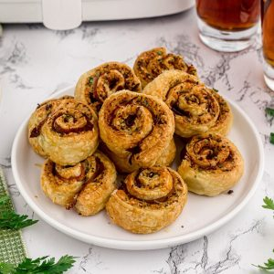 Large white plate full of golden pesto pinwheels served on a white marble table.