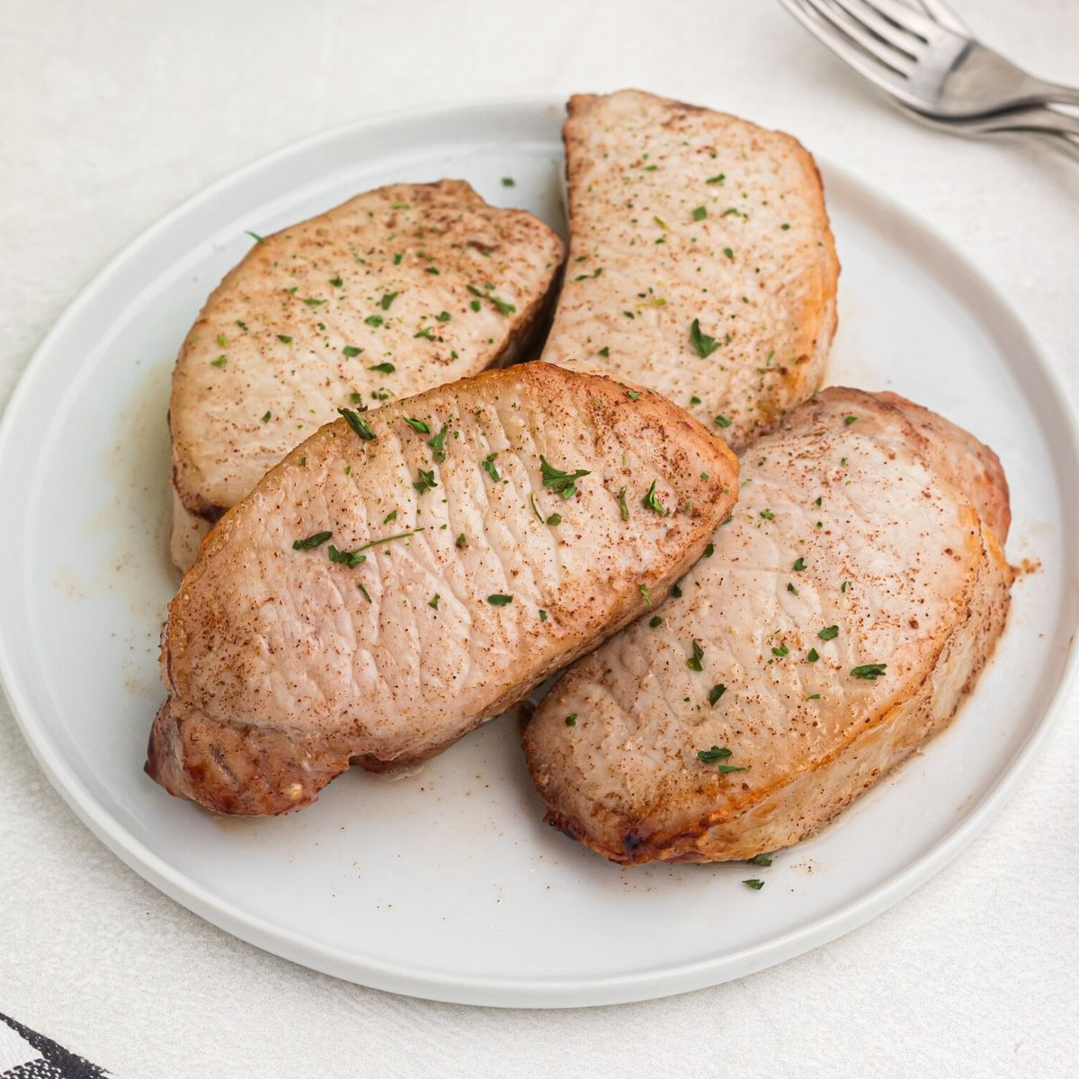 Cooked glazed pork chops cooked and served on a white plate, sprinkled with parsley flakes.