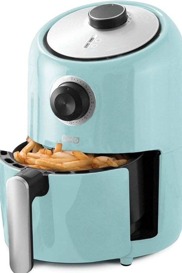 Dash air fryer with basket full of french fries.