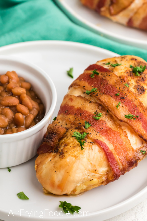 Bacon Wrapped chicken on a white plate with a side of beans.
