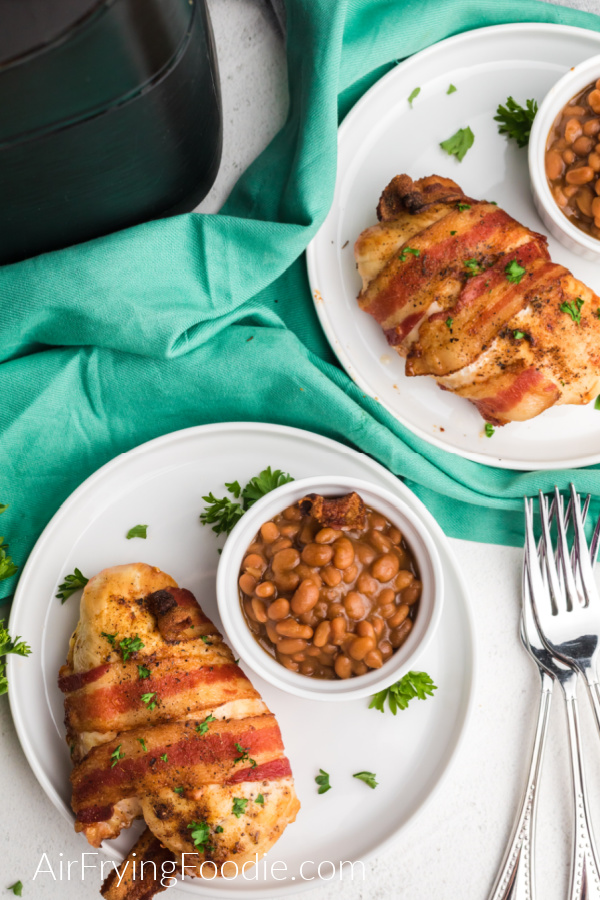 Bacon Wrapped Chicken made in the air fryer on a white plate with a side of baked beans.