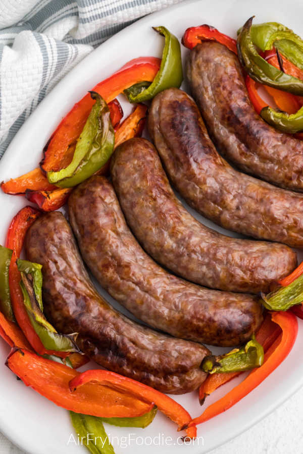 Air Fried Brats and peppers on a white plate ready to serve.