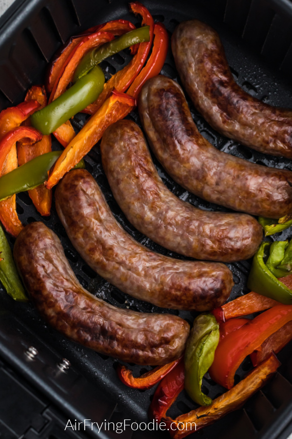 Air Fried Brats and Peppers in the basket of the air fryer.