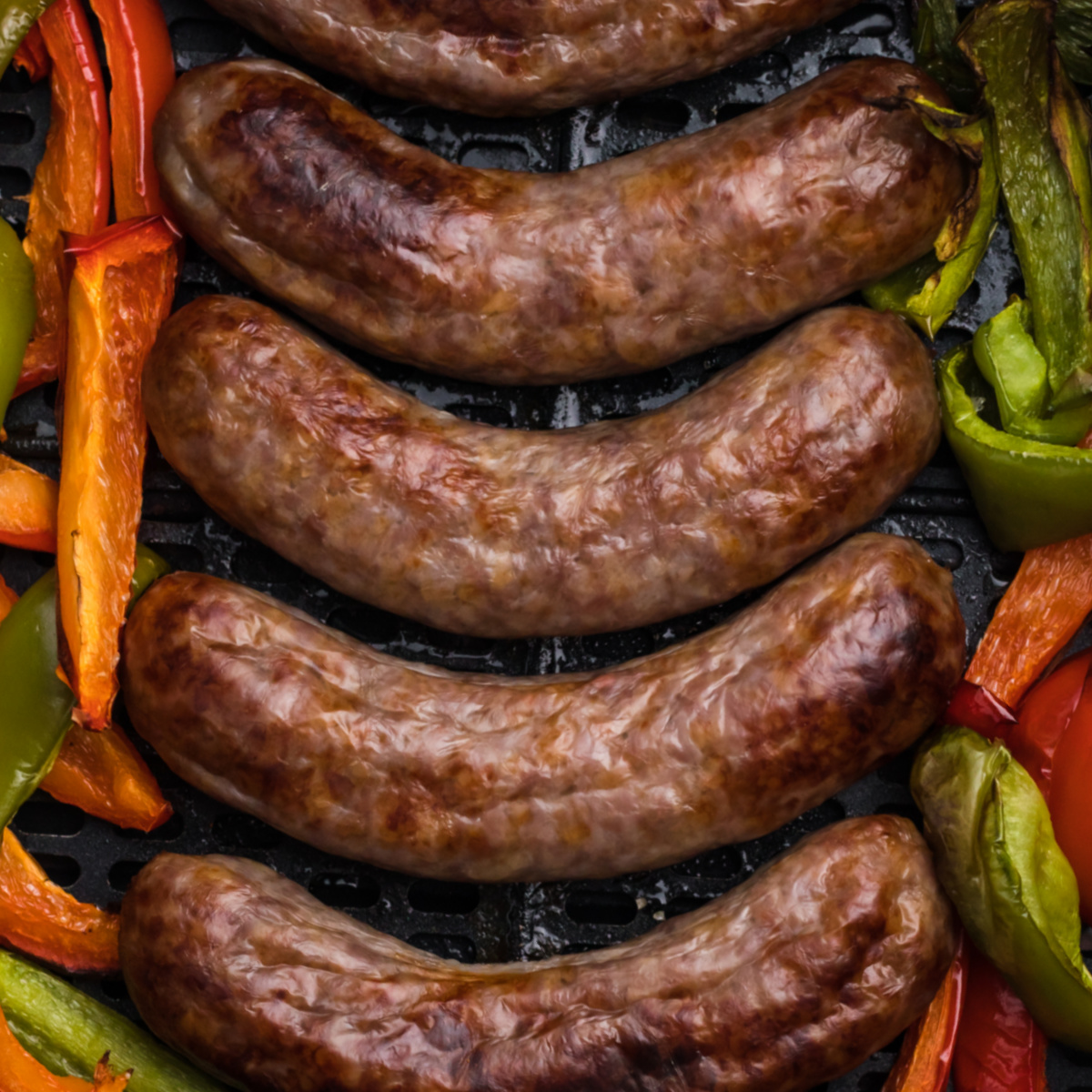 Brats and peppers in the basket of the air fryer.