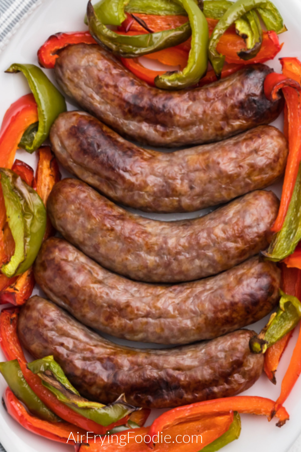 Brats made in the air fryer with cooked peppers on a white plate.