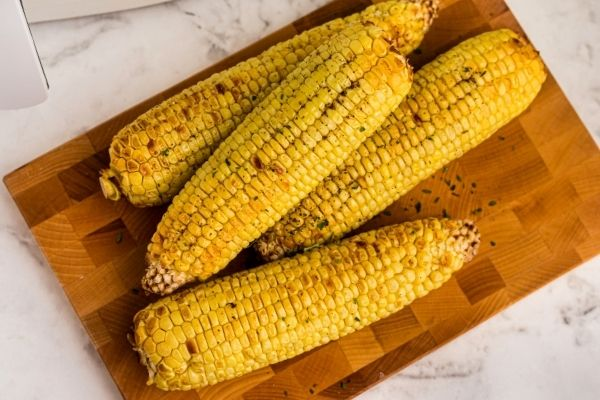 Golden yellow corn on the cob, seasoned on a wooden serving board.