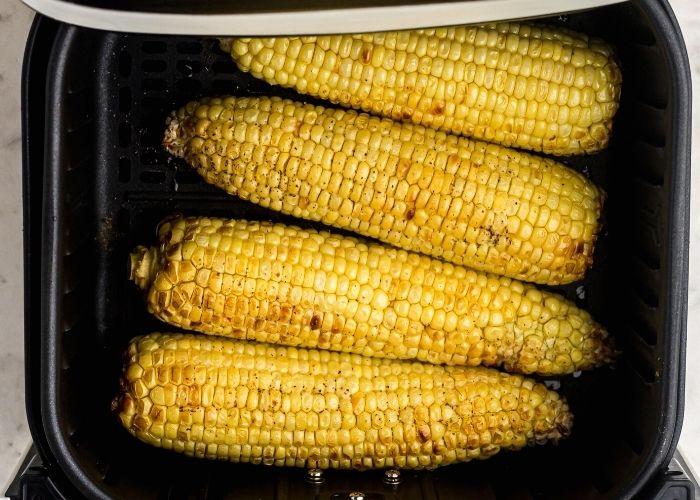 Golden juicy sweet corn, seasoned and cooked in an air fryer basket.