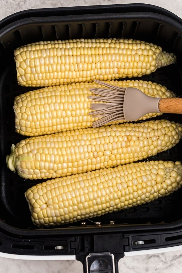 Ears of corn in the air fryer basket, being brushed with melted butter before cooking.