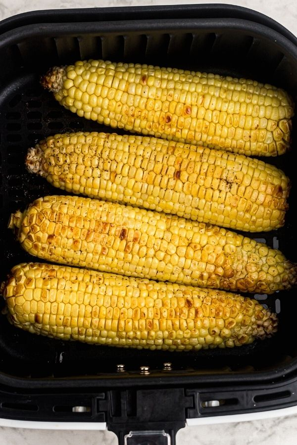 Golden cooked ears of corn in the air fryer basket.