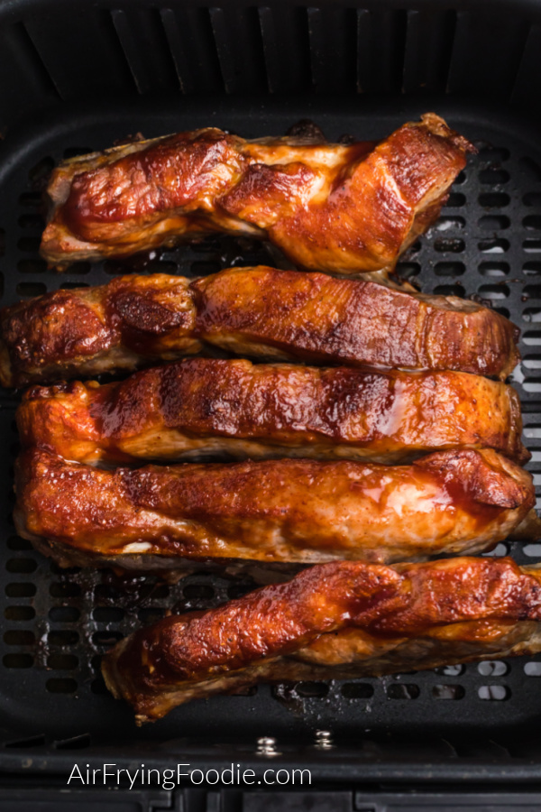 Fully cooked country-style ribs in the basket of the air fryer, ready to serve.