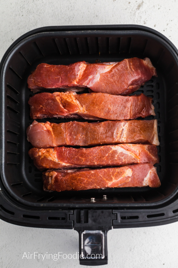 Seasoned country-style ribs in the basket of the air fryer, ready to cook.