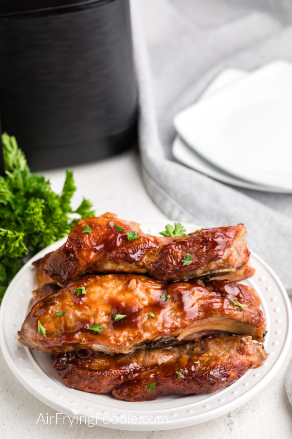 Air Fried Country Style Ribs on a white plate and with parsley sprinkled on top before serving.