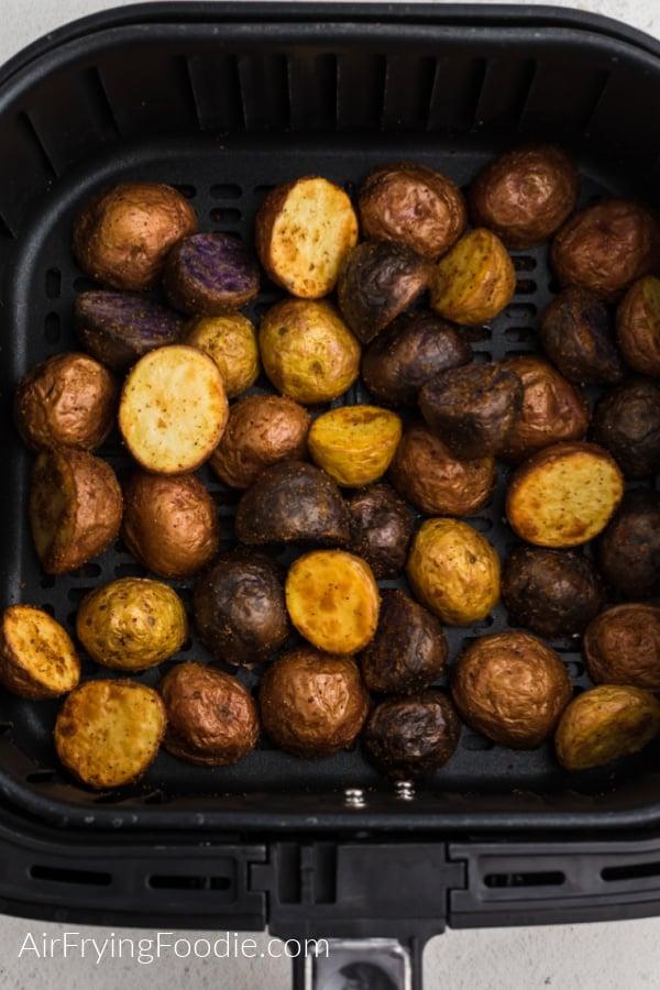 Seasoned Roasted potatoes in the air fryer basket.
