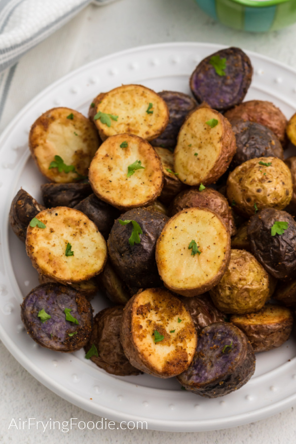 Air Fryer Roasted Potatoes on a white plate and topped with fresh parsley.