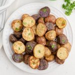 Air Fryer Roasted Potatoes in a white plate and garnished with fresh parsley. Ready to eat.