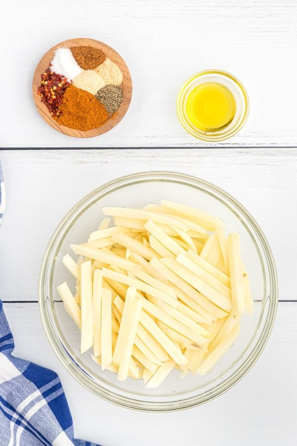 Ingredients needed to make seasoned fries. Spices, chopped potatoes, and olive oil.