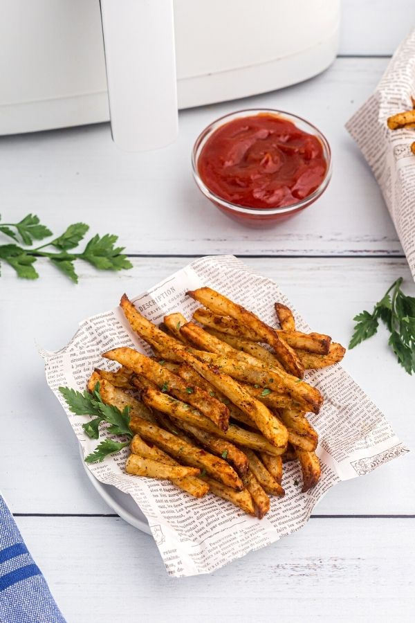 Serving of golden fries served on a white plate with paper and fresh parsley on the table.