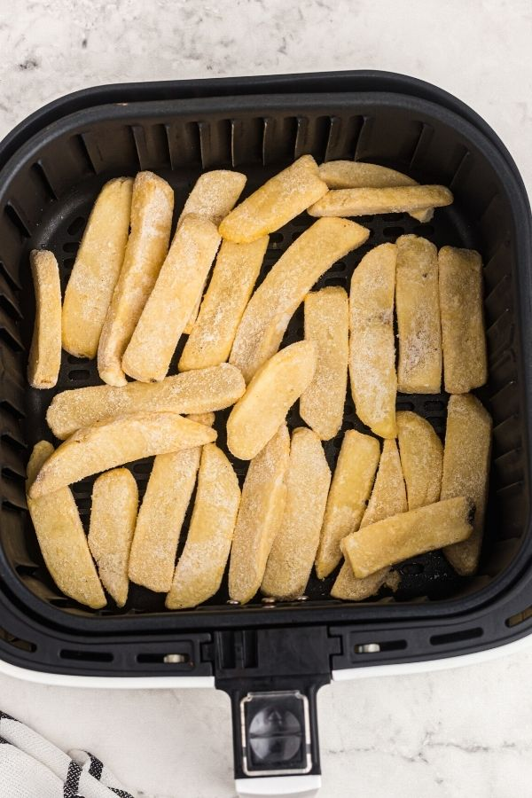 Frozen steak fries in the air fryer basket before being cooked.