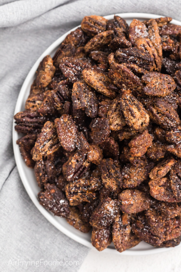 Close up photo of sugared pecans on a white plate ready to eat.