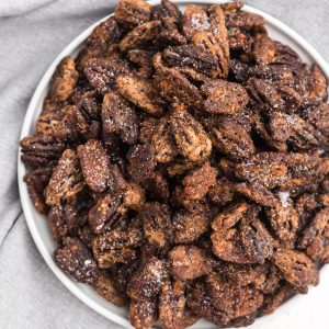 Overhead shot of sugared pecans made in the air fryer and served on a a white plate.