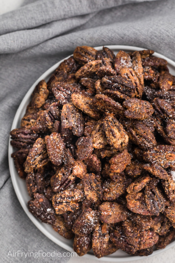 Air Fryer Sugar Pecans roasted in the air fryer, on a a white plate and sprinkled with a little sugar before serving.