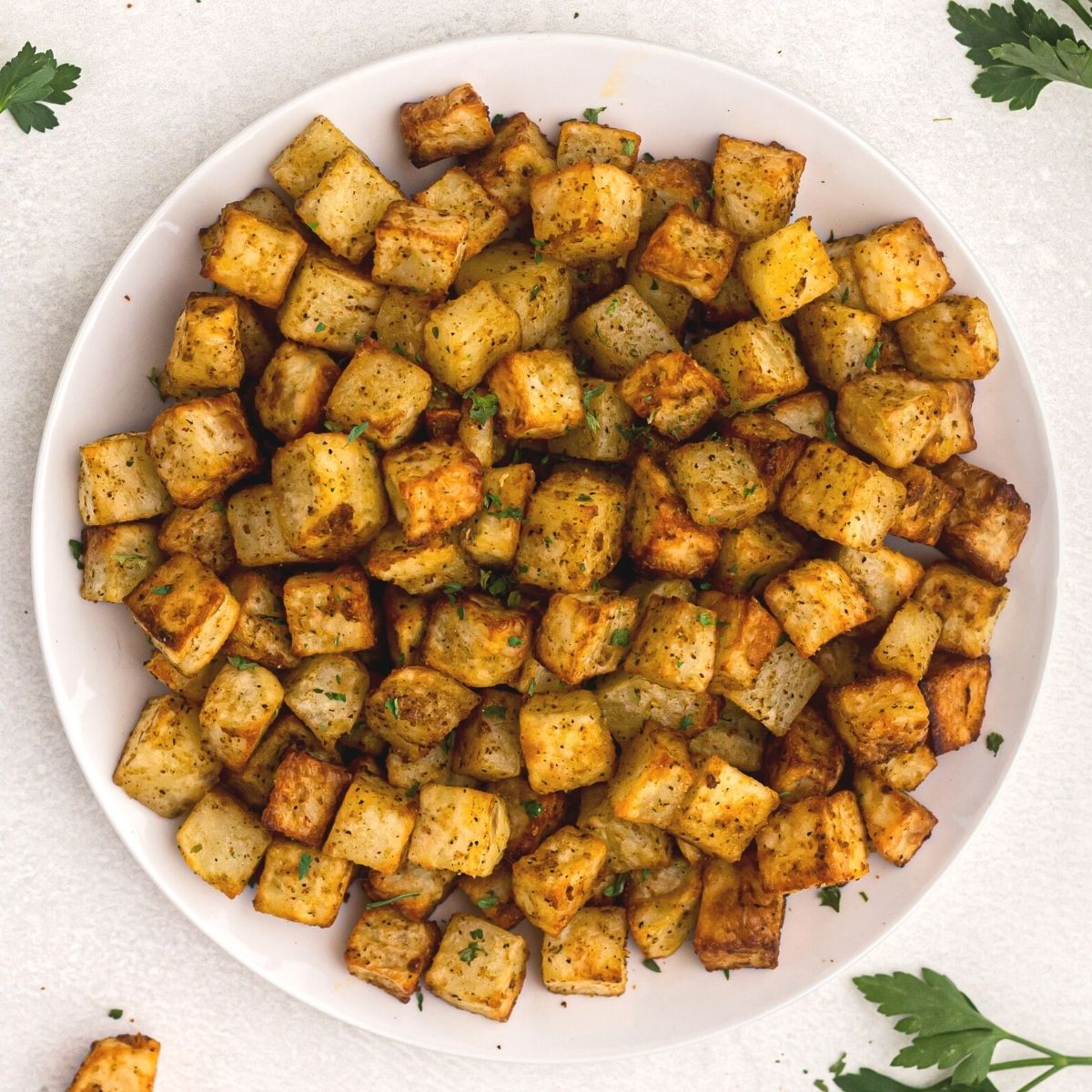 golden cubes of potatoes cut and cooked served on a white plate and garnished with parsley.